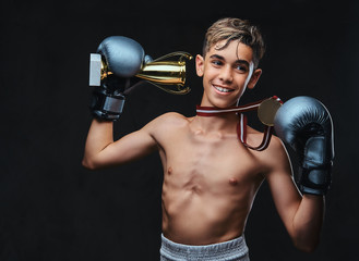Joyful young shirtless boxer champion wearing gloves holds a winner's cup and the gold medal. Isolated on a dark background.