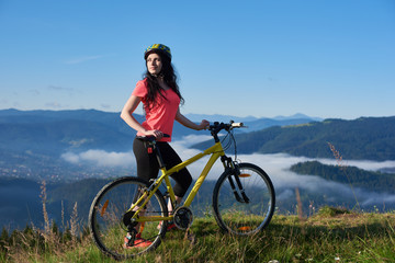 Attractive woman cyclist with yellow bike on a rural trail in the mountains, wearing helmet and red red t-shirt, enjoying morning haze in valley, forests on blurred background. Outdoor sport activity