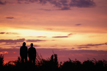 Silhouette of two men at sunset