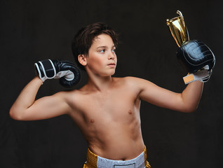 Young shirtless boxer champion wearing gloves holds a winner's cup showing muscles.