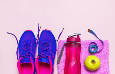 Fitness concept with Ultra violet pink female sneakers, water bottle, pink towel, apple on pastel pink background flat lay top view. Sports shoes, fitness, concept of healthy lifestile.