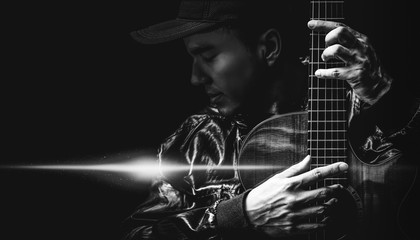 black and white portrait of asian handsome male musician posing on acoustic guitar