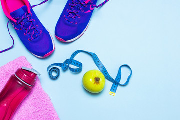 Fitness concept with Ultra violet pink female sneakers, water bottle, towel, apple on pastel blue background flat lay top view. Sports shoes, fitness, concept of healthy lifestile.