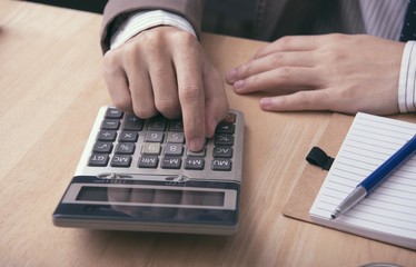 business accountant with calculator for calculate financial on office table. concept planning budget and audit.
