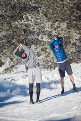 Two man warming up on snowy mountain