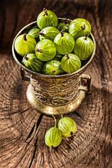 Gooseberries in metal bowl on vintage wooden background
