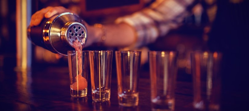 Waiter pouring cocktail drink into shot glasses at counter