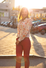 Positive brunette model wearing blouse and pink jacket posing at the evening city background