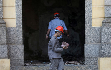 A worker carries a piece of a rock of the National Museum of Brazil in Rio de Janeiro