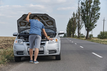 A young man near a broken car with an open hood on the roadside.