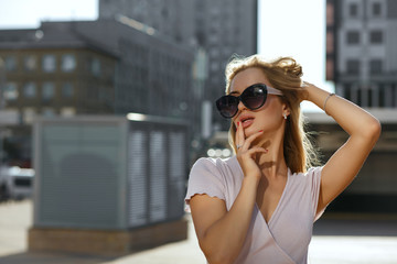 Sensual blonde woman wearing fashionable dress and sunglasses posing at the avenue in soft evening light. Space for text