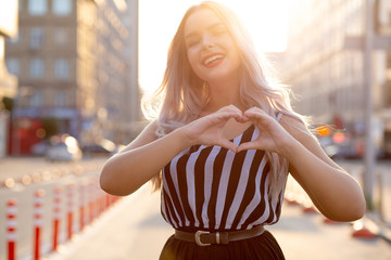 Happy blonde girl with red lips making heart sign with her fingers at the street