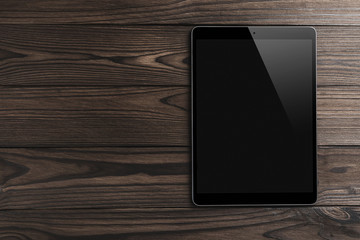 Black tablet computer on wooden dark background with space for text, flat lay