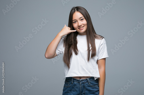 Portrait of a happy young Asian woman making a call me