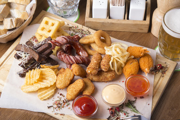 Beer snack with chicken nuggets,  onion rings and fried sausages with potato chips  and sauces