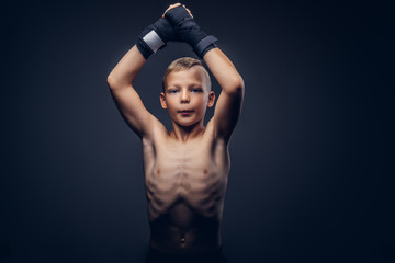 Young shirtless boy boxer wearing sports gloves posing in a studio.