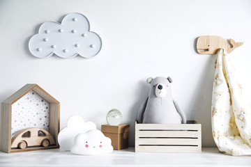 Stylish and cozy childroom with teddy bear, clouds and wooden car. Bright and sunny interior.