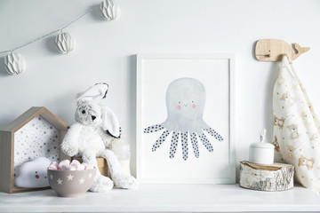 Stylish scandinavian newborn baby room with toys,  rabbit, cotton lamps and star. Modern interior with mock up photo frame.