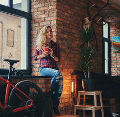 Sensual blonde hipster girl with long curly hair dressed in a fleece shirt and jeans holds a cup of morning coffee sitting on a window sill at a studio with loft interior.