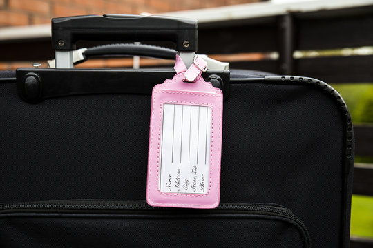 Pink feminine empty luggage tag attached to black baggage suitcase, fill in the tag, name, address, phone text. Lost, found design element concept.