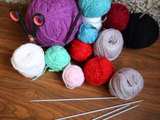 Balls of color yarn. Knitting needles and scissors. Wooden table background
