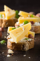 Canapes on bread with cheese, hazelnuts, Basil. Delicious appetizer with nuts for wine. Vegetarian gourmet food on dark background