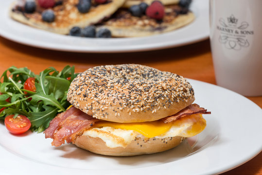Tasty fresh bagel with bacon, egg and cheese. Pancake in behind.