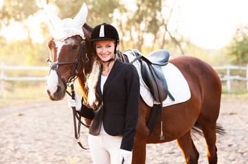 Beautiful blonde girl walks with horse