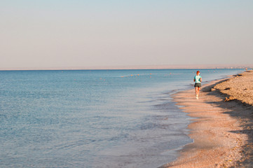 A girl on the beach makes a morning jog along the sea. Sport