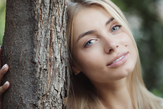 Woman leaning head to tree trunk, blue eyes pretty girl