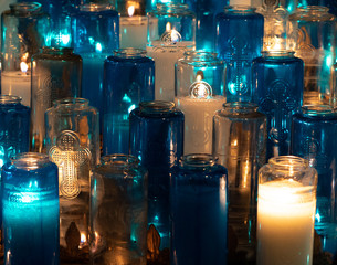Blue and White Religious Votive Candles with many lit.