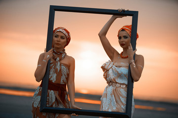 Girls traveler with wooden picture frame at colorful sea sunset.  Portrait of a Two Young women holding an empty frame.Summer vacation and travel concept.