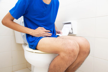 Man constipated suffering sitting on toilet