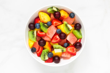 Zelfklevend Fotobehang Vruchten Bowl of healthy fresh fruit salad on white marble background. healthy food