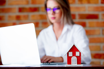 Young realtor with laptop computer and toy house. Brick wall on background
