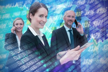 Composite image of businesswoman using tablet while colleagues
