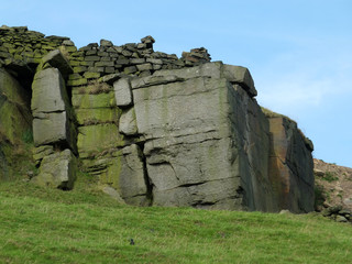 a large rock outcrop boulders with a stone wall along the top in yorkshire moorland