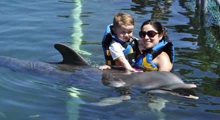 Child and girl with dolphin in blue water.
