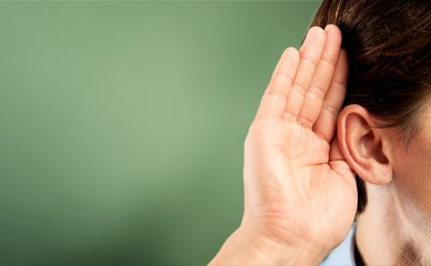 Businessman holds his hand near his ear and listening something