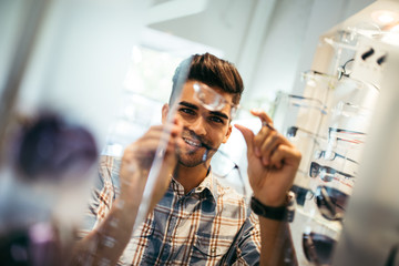 Handsome young man choosing eyeglasses frame in optical store.