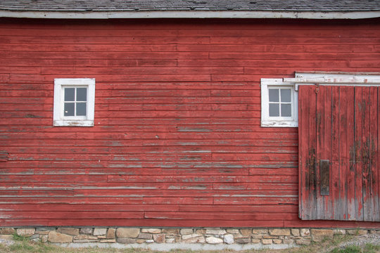 Side of an old red barn with white framed square windows and sliding door