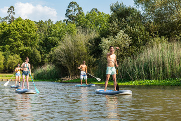 Men and women stand up paddleboarding