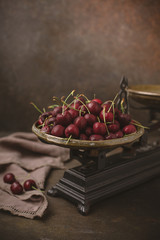 Freshly Picked Cherries in an Antique Scale on Warm Brown Background