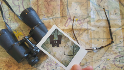 Man holding a polaroid photo over a map with binoculars