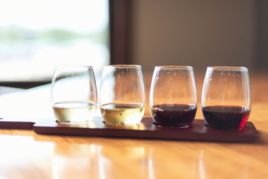 Tasting a variety of wines from a flight at a local vineyard - wine tasting event