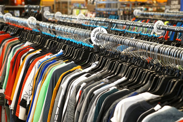 rows of clothes hanging in the rack of store