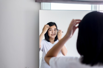 Woman eyebrow correction shape with brush front of mirror,Makeup and beautiful woman face