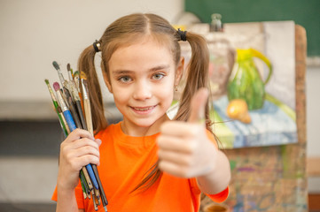 Little girl painter with brushes and easel at school and showing thumbs up