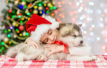 little girl in red christmas hat hugging puppy on a background of the Christmas tree