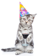 Tabby kitten in party hat holding glass of red wine. isolated on white background